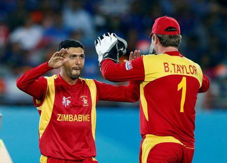 Zimbabwe's Butt celebrates with teammate Taylor after the dismissing of India's Kohli during their Cricket World Cup match at Eden Park in Auckland