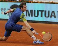 British player Andy Murray returns the ball to German player Florian Mayer during their tennis match at the Madrid Masters at the Magic Box (Caja Magica) sports complex in Madrid on May 7, 2013. Murray won 7-6 (13/11), 7-6(7/3)