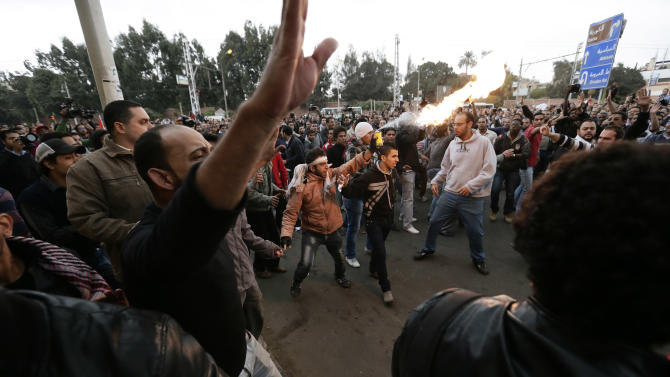 Egyptian President Mohammed Morsi's supporters and opponents clash outside the presidential palace, in Cairo, Egypt, Wednesday, Dec. 5, 2012. Wednesday's clashes began when thousands of Islamist supporters of Morsi descended on the area around the palace where some 300 of his opponents were staging a sit-in. (AP Photo/Hassan Ammar)