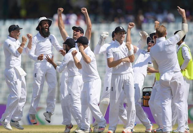 England players including captain Alastair Cook (arms aloft) celebrate after beating Bangladesh during the final day's play of the first Test match in Chittagong on October 24, 2016