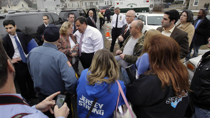 """New Jersey Gov. Chris Christie, center left, greets residents in Union Beach, N.J., Tuesday, Feb. 5, 2013, outside a center where Federal Emergency Management Agency and state agencies were helping with claims. Christie says the National Flood Insurance Program's handling of claims in New Jersey has been """"a disgrace,"""" complaining that the program has been far too slow to resolve claims from Superstorm Sandy, with 70 percent of cases unresolved three months after the disaster. (AP Photo/Mel Evans)"""