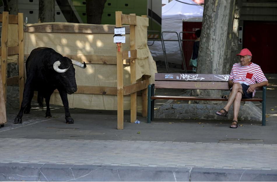 A man sits next to a stuffed bull used for pictures for tourists in Pamplona