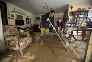 Family members sweep murky water from their flooded house in Beit Hefer on January 9, 2013. The worst storms in a decade left swathes of Israel and Jordan under a blanket of snow and parts of Lebanon blacked out on Thursday, bringing misery to a region accustomed to temperate climates.