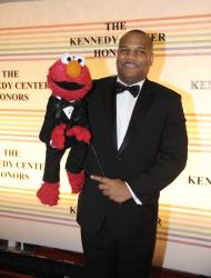 """FILE - This Dec. 4, 2011 file photo shows """"Sesame Street"""" character Elmo and puppeteer Kevin Clash arrive at the Kennedy Center for the Performing Arts for the Kennedy Center Honors gala performance in Washington. Clash has taken a leave of absence from the popular kids' show following allegations that he had a relationship with a 16-year-old boy. Sesame Workshop says Kevin Clash denies the charges, which were first made in June by the alleged partner, who by then was 23. In a statement issued Monday, Nov. 12, 2012, Sesame Workshop says its investigation found the allegation of underage conduct to be unsubstantiated. (AP Photo/Kevin Wolf, file)"""