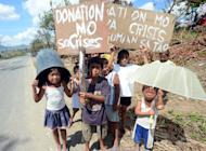 Children beg for alms on a roadside in the town of Osmena in Compostela Valley province on Sunday. Desperate families begged for food, days after a typhoon brought death and destruction to parts of a southern Philippine island, as the storm returned to the north of the country