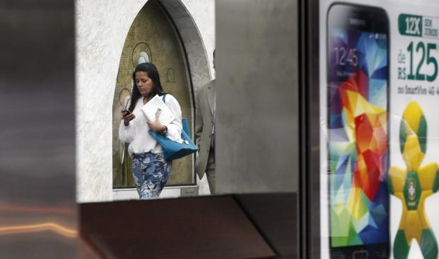 A woman uses her mobile phone next to a mobile company advertisement in Sao Paulo