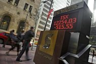 People walk by a sign displaying TSX information in Toronto, September 15, 2008. REUTERS/Mark Blinch