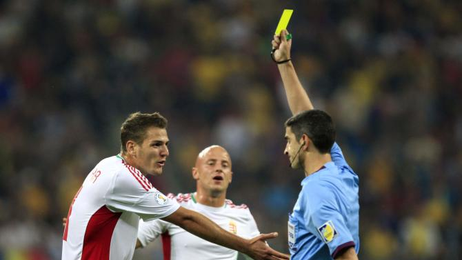 Hungary's Kocsmar receives a yellow card from the referee Mallenco of Spain during their 2014 World Cup qualifying soccer match against Romania in Bucharest's National Arena