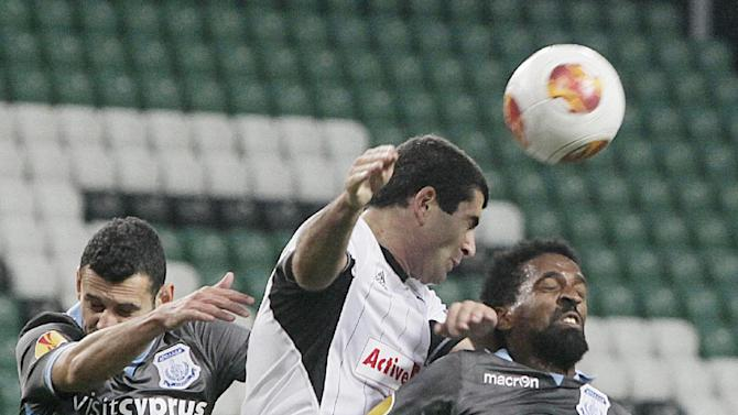 Rachid Hamdani,right, and Christos Karipidis,left, of Apollon Limassol FC challenges for the ball with Vladimer Dvalihvili.center, , left, of Legia Warsaw, during their Europa League group J soccer match in Warsaw, Poland, Thursday, Oct. 3, 2013