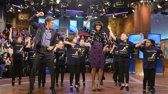 "This image released by Sony Pictures television shows first lady Michelle Obama, center, and host Dr. Mehmet Oz dancing with third graders from the Terence C. Reilly #7 School in Elizabeth, N.J. to demonstrate fun ways to keep moving in the classroom during a taping of ""The Dr. Oz Show,"" on Friday, Feb. 22, 2013 in New York.  The school came to the attention of the White House because of their novel approach to include spontaneous dance breaks throughout the day. The episode will air on Thursday Feb. 28. (AP Photo/Sony Pictures Television, Barbara Nitke)"