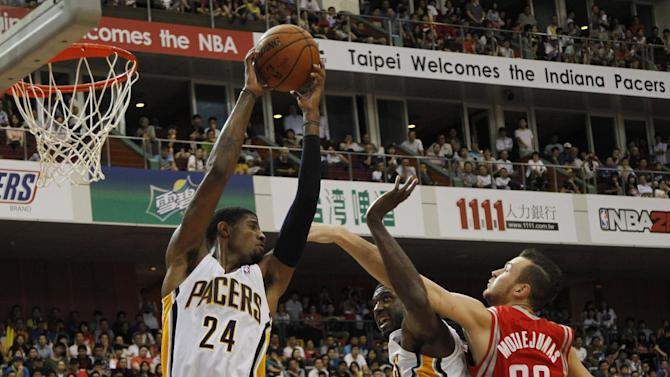 NBA Indiana Pacers Paul George (24) grabs the ball at the net from Houston Rockets Donatas Montiejunas (20) while he's blocked by Pacers Roy Hibbert during a preseason game in Taipei, Taiwan, Sunday, Oct. 13, 2013. The Rockets beat the Pacers 107-98