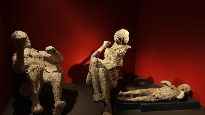 Casts of a family of two adults and two children who died together in an alcove in Pompeii, made by filling plaster in the void left by their bodies, are seen during a photo call for the upcoming exhibition entitled 'Life and death Pompeii and Herculaneum', at the British Museum in central London, Tuesday, March 26, 2013. The exhibition about the two Roman cities, buried by a catastrophic volcanic eruption of Mount Vezuvius in 79 AD, will run at the museum from March 28 to Sept. 29, 2013. (AP Photo/Lefteris Pitarakis)