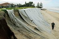 Felt sheeting is seen draped over sandhills to help slow the progress of erosion in front of the Meridien holiday apartments at Old Bar Beach at the coastal town of Old Bar in Australia's New South Wales state. Old Bar is the most rapidly eroding and at-risk piece of coast in populous New South Wales state, losing an average one metre of seafront every year