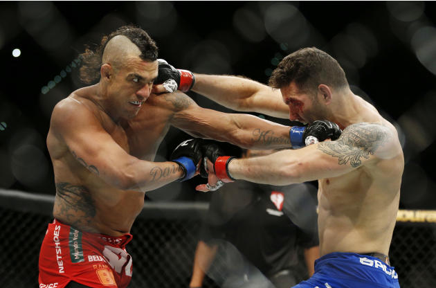 Chris Weidman, right, and Vitor Belfort trade blows during their middleweight mixed martial arts bout at UFC 187 on Saturday, May 23, 2015, in Las Vegas. (AP Photo/John Locher)