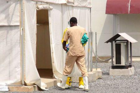 A health worker enters a tent in an Ebola virus treatment center in Conakry