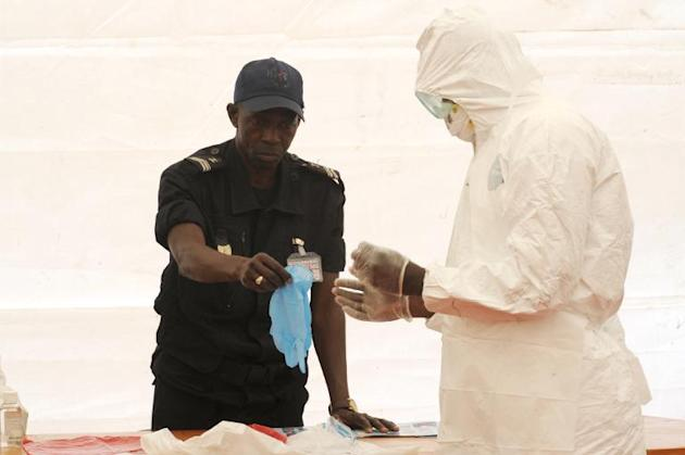 A Senegalese hygienist demonstrates how to protect oneself against the Ebola virus on April 8, 2014 at Dakar airport