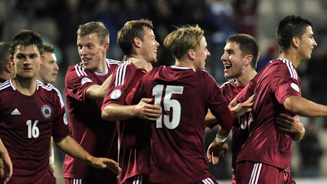 Latvia's team players celebrate after scoring a goal against Slovakia during their World Cup 2014 Group G qualification match in Riga, Latvia, on Tuesday. Oct. 15, 2013
