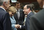 (L-R) Italian Prime Minister Mario Monti and Spanish Prime Minister Mariano Rajoy (C) look on as German Chancellor Angela Merkel and French President Francois Hollande shake hands. Hollande stepped up his crusade Thursday to convince eurozone nations to share debt between rich and poor despite resistance from Germany