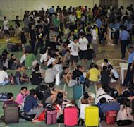 Hundreds of Taiwanese and mainland Chinese people rounded up by Philippine police on suspicion of being involved in a telephone scam wait to be processed by authorities at a police station in the town of Canlubang, south of Manila, on August 23. They suspects could be charged under a law penalising the use of telecom systems to commit fraud, Reyes said and could face six to 20 years in jail