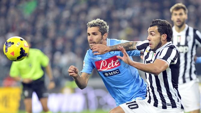 Juventus forward Carlos Tevez, of Argentina, challenges for the ball with Napoli' s Valon Berhami, during a Serie A soccer match between Juventus and Napoli at the Juventus stadium, in Turin, Italy, Sunday, Nov, 10, 2013
