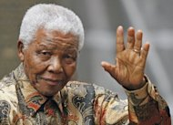 "Nelson Mandela waves to the media as he arrives outside No. 10 Downing Street in central London,on August 28, 2007. Mandela's family to solve an increasingly bitter dispute ""amicably"", weighing in for the first time on a feud over the ailing anti-apartheid icon's final resting place"