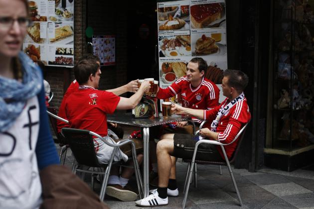 Bayern Munich supporters make a toast as they hang out in central Madrid