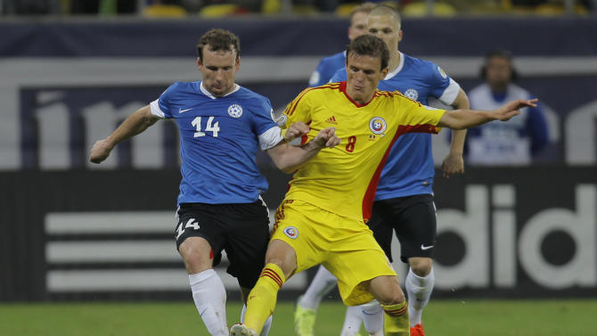 Konastantin Vassiljev, left, of Estonia and Costin Lazar, right, of Romania challenge for the ball during the World Cup Group D qualifying soccer match at the National Arena stadium in Bucharest, Romania, Tuesday, Oct. 15, 2013
