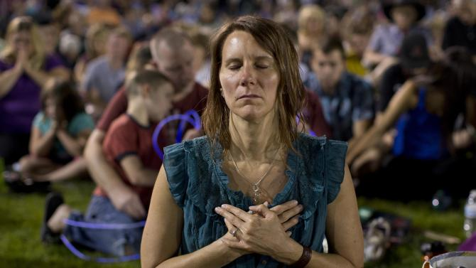 Leta Liberick closes her eyes in prayer during a candlelight vigil in Prescott, Ariz. on Tuesday, July 2, 2013 to honor the 19 Granite Mountain Hotshot firefighters who were killed by an out-of-control blaze near Yarnell, Ariz. on Sunday. (AP Photo/Julie Jacobson)
