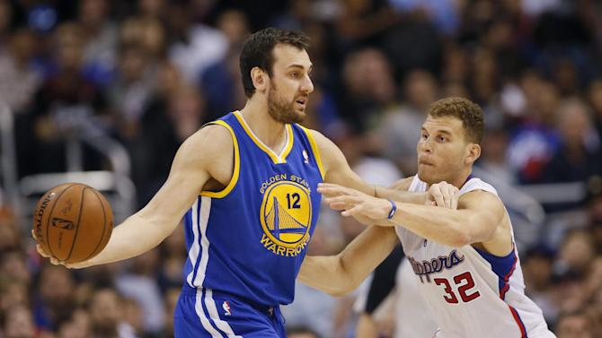 Golden State Warriors' Andrew Bogut, left, controls the ball as Los Angeles Clippers' Blake Griffin defends during the first half of an NBA basketball game in Los Angeles, Wednesday, March 12, 2014