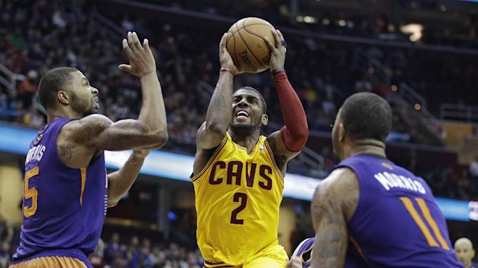 Cleveland Cavaliers' Kyrie Irving (2) goes up for a shot against Phoenix Suns' Marcus Morris and Markieff Morris (11) in the fourth quarter of an NBA basketball game, Sunday, Jan. 26, 2014, in Cleveland. Irving led the Cavaliers with 24 points in a 99-90 loss to Phoenix