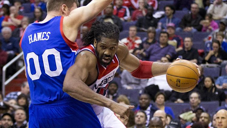 Washington Wizards power forward Nene, right, drives past Philadelphia 76ers center Spencer Hawes during the second half of an NBA basketball game on Monday, Jan. 20, 2014 in Washington. The Wizards defeated the 76ers 107-99