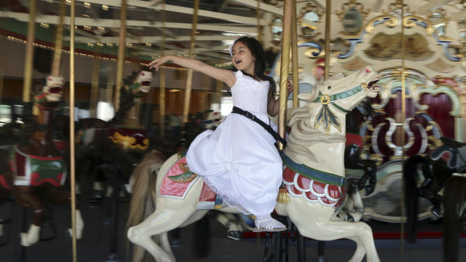 A child rides the B & B Carousel on the Coney Island's boardwalk, Wednesday, June 19, 2013 in New York. Eight months after Superstorm Sandy hit New York City, Coney Island's rides, eateries and beach are getting plenty of visitors, and there are even a few new attractions like a carousel and a store for fans of the Nets basketball team. (AP Photo/Mary Altaffer)