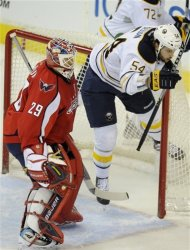 Buffalo Sabres right wing Zack Kassian (54) runs into the net as Washington Capitals goalie Tomas Vokoun (29), of the Czech Republic, looks on during the first period of an NHL hockey game, Friday, Dec. 30, 2011, in Washington. (AP Photo/Nick Wass)