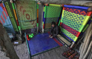 A Pakistani vendor weaves cot with nylon threads at his shop in Peshawar, Pakistan on Monday, Nov. 14, 2011. (AP Photo/Mohammad Sajjad)