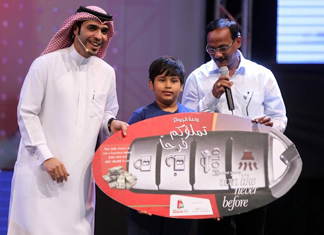 Madhup Roshan (C), an Indian student residing in Dubai, walks away with two luxurious Infiniti models, the JX35 and G25, and a cash prize of Dh100,000 during the DSF daily raffle draw.