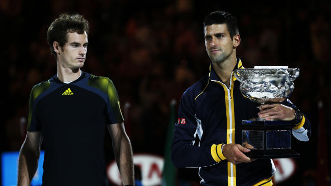 Runner-up Andy Murray of Britain looks on as Novak Djokovic of Serbia poses with the Norman Brookes Challenge Cup after their men's singles final match at the Australian Open tennis tournament in Melbourne