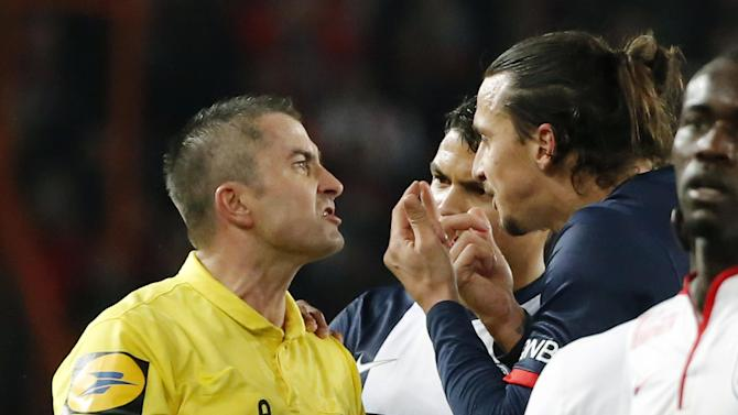 Referee Fredy Gautrel, left, argues with Paris-Saint-Germain's Zlatan Ibrahimovic of Sweden, right, after he was booked during a French league one soccer match between Paris-Saint-Germain and Lille at Parc des Princes stadium in Paris, Sunday Dec. 22, 2013.  Ibrahimovic and Lille's Antonio Mavubat were booked for shoving each other