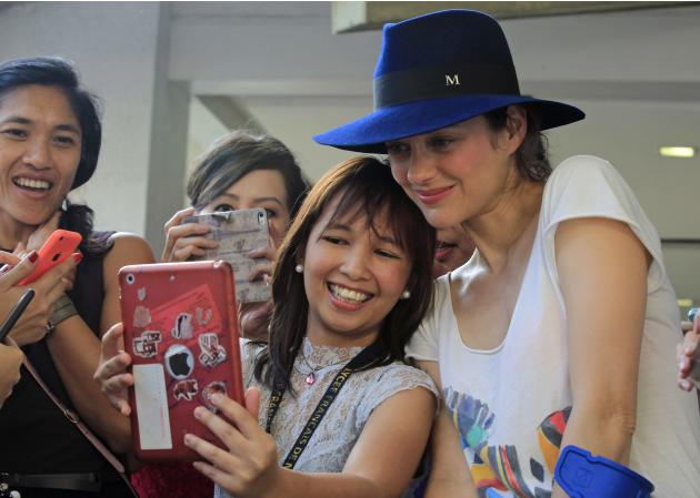 French actress Cotillard poses for a picture with a fan during a visit to a French school in Manila