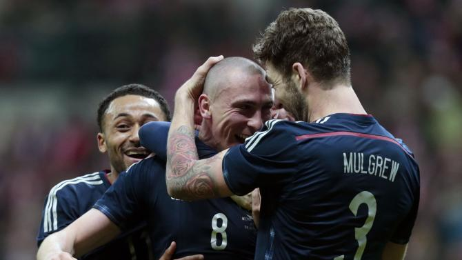 Brown of Scotland celebrates with his teammates Anya and Mulgrew after scoring a goal against Poland during their international friendly match in Warsaw