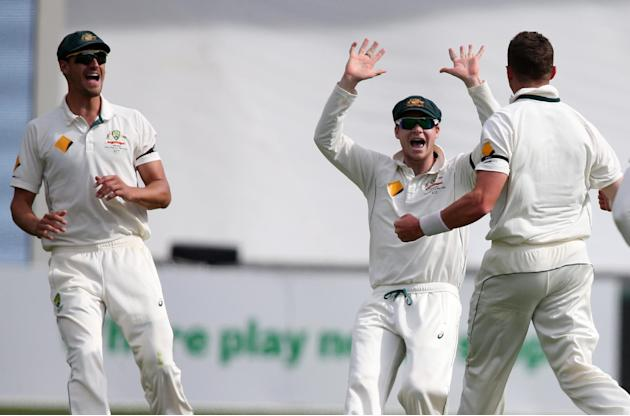 Australia's Peter Siddle, is congratulated by teammates Steve Smith, centre, and Australia's Mitchell Starc, left, after taking the wicket of New Zealand's Ross Taylor during their cricket