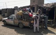 Pakistani residents pack belongings into a van as they prepare to flee Miranshah in the North Waziristan tribal agency, on June 13, 2014