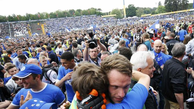 Damstadt's Mathenia celebrates with fans and teammates after winning their German Bundesliga second division soccer match against Sankt Pauli in Darmstadt