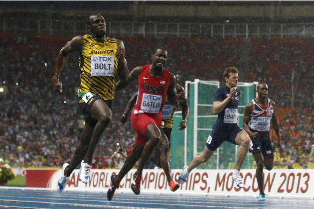 Jamaica's Usain Bolt, left, crosses the finish line to win the gold in the Men's 100-meter final ahead of USA's Justin Gatlin, center, at the World Athletics Championships in the Luzhniki stadium in M