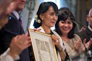 Myanmar pro-democracy leader Aung San Suu Kyi poses after receiving an honorary citizen award, beside Paris' deputy mayor Anne Hidalgo (R) at the Paris City Hall. Suu Kyi, nearing the end of her triumphant Europe tour in France, accepted another award Wednesday as she became an honorary citizen of Paris