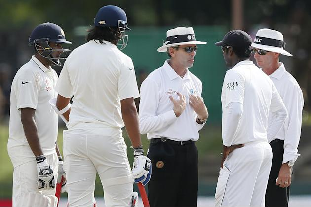 Umpire Llong talks to Sri Lanka's captain Mathews after an argument between India's batsman Sharma and Sri Lanka's bowler Prasad during the fourth day of their third and final test cricket