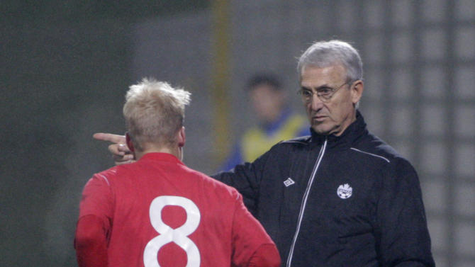 Canada's head coach Benito Floro right, instructs Canada's Kyle Bekker during a friendly soccer match between Slovenia and Canada, in Celje, Slovenia, Tuesday, Nov. 19, 2013