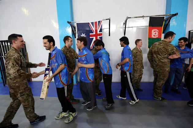 An Australian soldiers shake hands with Afghan local employees after an exhibition cricket match at NATO headquarters in Kabul, Afghanistan, Monday, March, 2, 2015. After setting up a target of 113, t