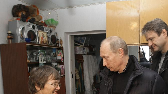 Russian Prime Minister Vladimir Putin, second right, talks with a local resident at her home damaged by a flood in the town of Novomikhailovsky, in the Krasnodar region, southern Russia, Friday, Oct. 22, 2010. Putin arrived in the Krasnodar region to inspect cleanup works in the area hit by floods after torrential rains. At right is Krasnodar region governor Alexander Tkachev. (AP Photo/RIA-Novosti, Alexei Nikolsky, Pool)