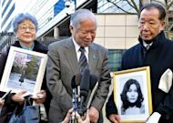 This file photo shows Shigeru Yokota (C) answering questions from reporters as his wife Sakie Yokota (L), with a picture of their daughter Megumi, and Shigeo Iizuka (R), with a picture of his sister Yaeko Taguchi, both women who were abducted by North Korea, look on following their meeting with US State Secretary Hillary Clinton at the US Embassy in Tokyo, in 2009