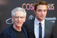 "British actor Robert Pattinson (R) and Canadian director David Cronenberg pose for fans as they arrive for the premiere of the film ""Cosmopolis"" in Berlin on May 31, 2012. The film directed by Canadian director David Cronenberg is set to open in the German cinemas. AFP PHOTO / JENS KALAENE GERMANY OU T"